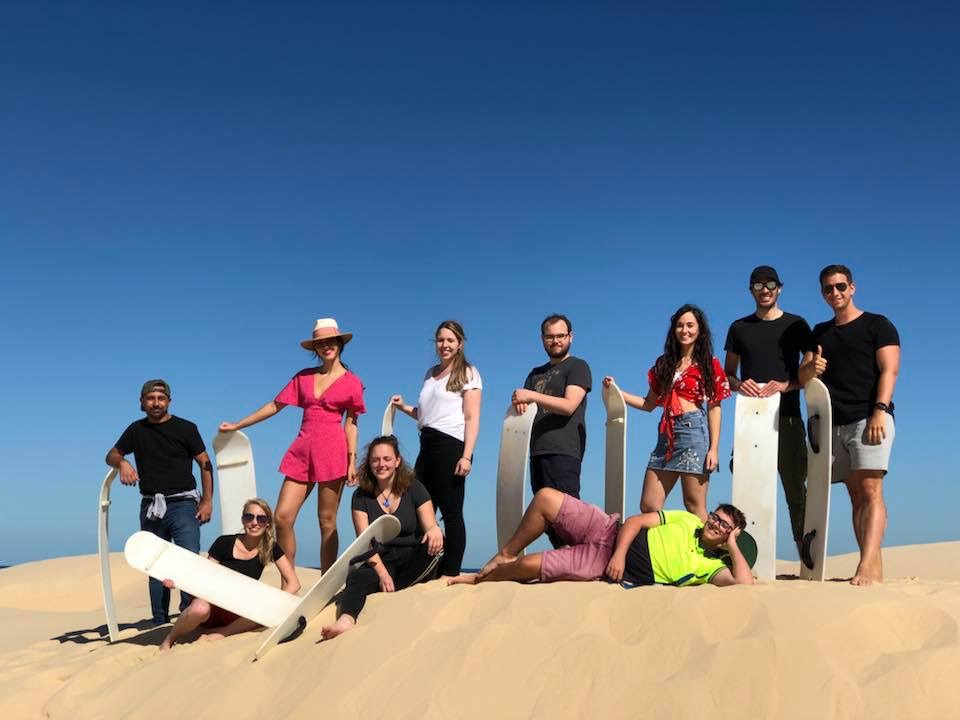 A school group enjoys some sandboarding after learning about the dune ecosystem